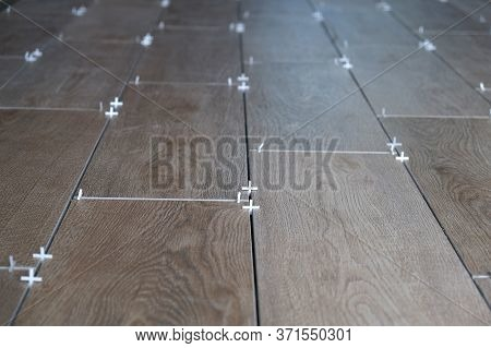 The Worker Puts Ceramic Tiles On The Construction Site