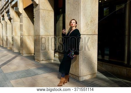 Stylish Outfit. Elegant Woman With Red Hair In Elegant Clothes And Luxurious Coat, Walking By City.