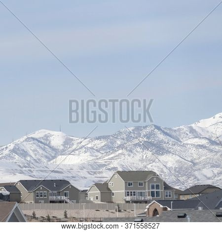 Square Frame Neighborhood In South Jordan City Against Snowy Wasatch Mountains And Cloudy Sky