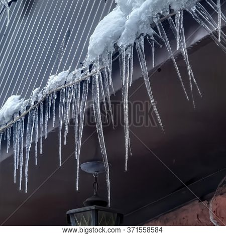 Square Frame Spiked Icicles At The Edge Of Pitched Gray Roof With Clumps Of Snow In Winter
