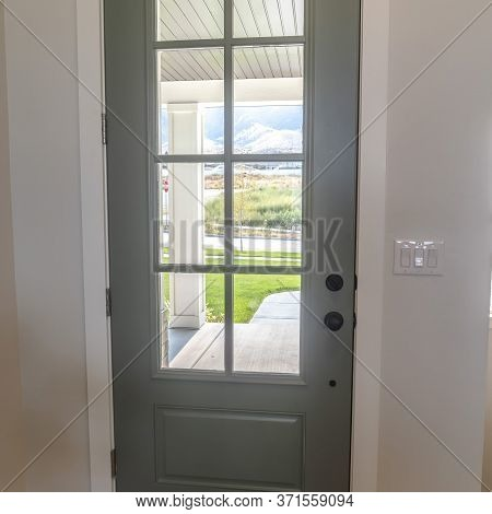 Square Front Door With Balck Knob And Glass Panes Against White Wall And Wood Floor