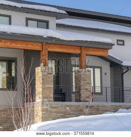 Square Home With Gray Wall And Front Porch Surrounded By Snowy Wasatch Mountain Terrain