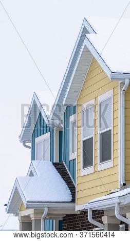 Vertical Townhome Exterior With Snowy Gable Valley Roof Against Overcast Sky In Winter