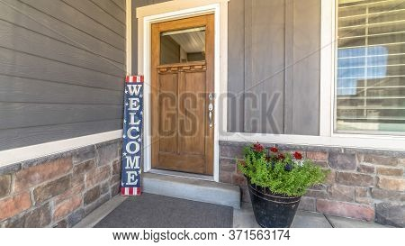 Panorama Frame Brown Front Door With Glass Pane And Welcome Sign Against Gray And Stone Wall