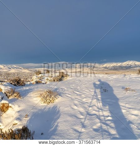Square Frame Snowy Hilltop Over Looking Utah Vally Community And Mountain Against Blue Sky