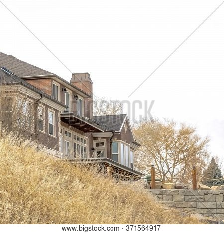 Square Crop Grassy Hill With Huge Houses And Retaining Wall Against Cloudy Sky Background