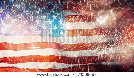 Patriotic holiday. The USA are celebrating 4th of July. American flag on background of fireworks.