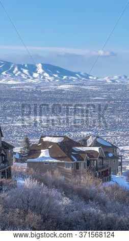 Vertical Crop Snow Falling On Wasatch Mountains With Homes On Frosted Terrain In Winter