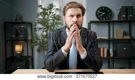 Front View Of Thoughtful Businessman In Classic Wear Sitting At Desk In Office With Steepling Hands