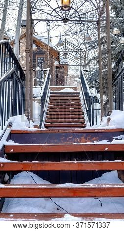 Vertical Frame Close Up Of Stairway On Snow Covered Slope With Buildings And Trees Background