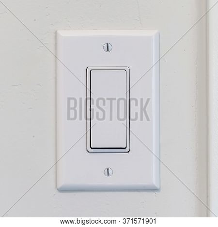 Square Frame Electrical Rocker Light Switch With Flat Broad Lever On White Interior Wall