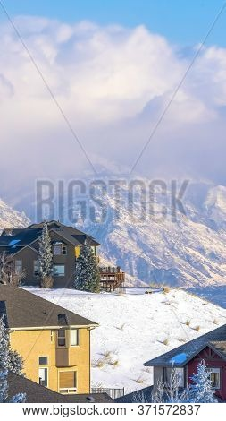 Vertical Beautiful Mountain Homes Against Snowy Wasatch Peaks And Cloudy Blue Sky
