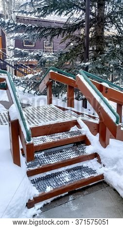 Vertical Crop Stairs With Green Handrails And Grate Metal Treads Built On Hill With Fresh Snow