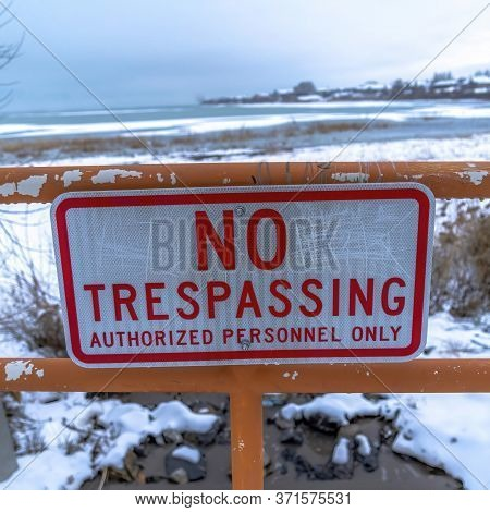 Square Close Up Of No Trespassing Signage With Snowy Utah Lake Background In Winter