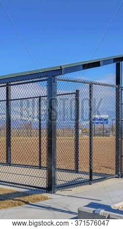 Vertical Baseball Field Dugout With Slanted Roof And Chain Link Fence On A Sunny Day