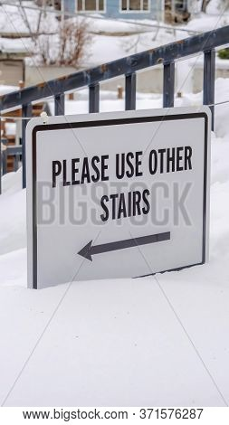 Vertical Frame Stairs Buried In Winter Snow With Sign That Reads Please Use Other Stairs