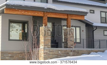 Panorama Frame Home With Gray Wall And Front Porch Surrounded By Snowy Wasatch Mountain Terrain