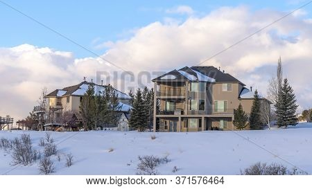 Panorama Homes Against Clouds And Blue Sky At Wasatch Mountains Neighborhood In Winter