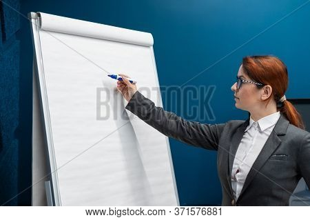 Friendly Woman In A Business Suit Writes On A Blank White Board With Marker. Red-haired Girl Makes A