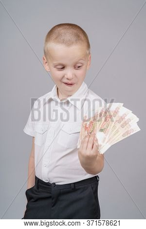 Cute Short-haired Boy Boy 7 Years Old Holds A Pack Of Russian 5000 Rubles In His Hands And Looks In