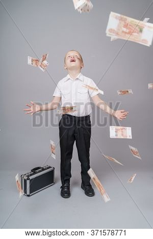 Cute Short-haired Boy Boy 7 Years Old With Black Suitcaseand Throwing Money Rubbles Cash. Overspend.