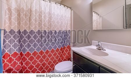 Panorama Home Bathroom With Toilet Vanity Area And Bathtub Conceled By Colorful Curtain
