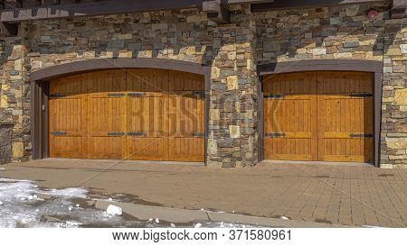 Panorama Facade Of Home Featuring Two Hinged Wooden Garage Doors And Stone Brick Wall