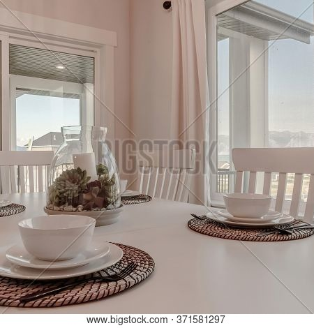 Square Dining Table With Tableware And Woven Placemat Arranged Around A Centerpiece