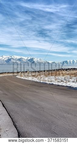 Vertical Crop Curvy Road Amid Snowy Terrain With Scenic Wasatch Mountains And Utah Lake View