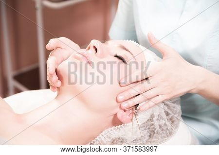 A Professional Female Massage Therapist Does A Facial Massage To A Client In A Spa Facial Care Salon
