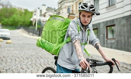 Young Delivery Woman In Helmet With Thermo Bag Or Backpack Looking At Camera, Riding A Bike Along Th