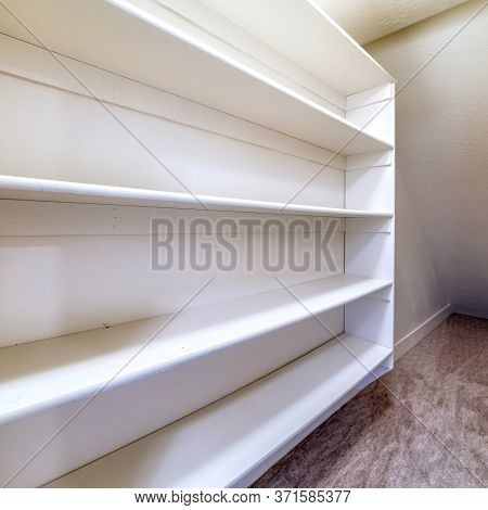 Square Small Walk In Closet With Empty Long Cabinet Shelves Under Slanted Ceiling