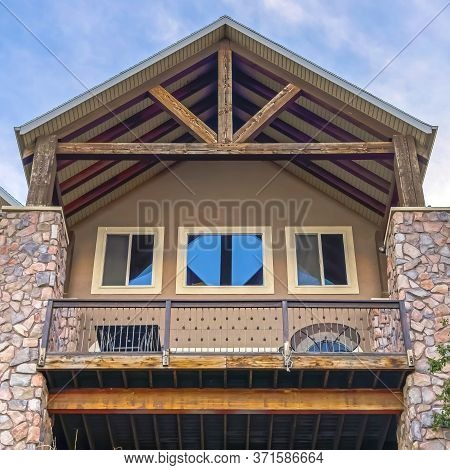Square Gable Roof With Wooden Beams Over Balcony And Porch With Square Stone Columns