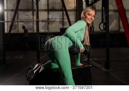 Young Beautiful Woman Doing One-arm Dumbbell Back Exercise On Bench. Athletic Blonde Girl In The Gym