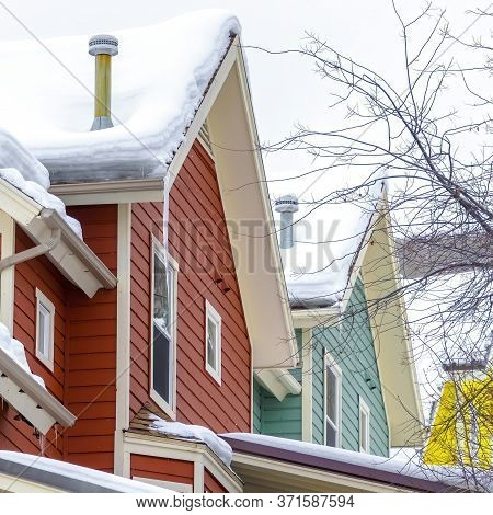 Square Homes Exterior With Snowy Roofs And Colorful Wall Sidings Against Hill And Sky