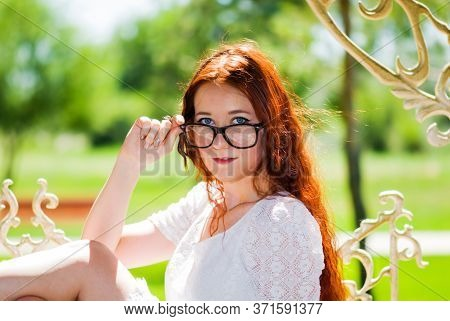 A Happy Red-haired Girl Adjusts Her Glasses In A Large Black Frame, Sitting In A Gazebo In Nature Wi