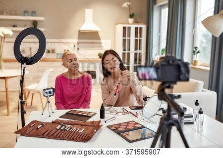 Asian Female Blogger Showing Products While Applying Makeup On Woman Face Using Cosmetics On The Tab