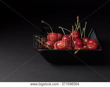 Organic Cherries In A Black Bowl. Ripe Berries On A Black Background.