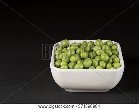 Organic Green Peas In A White Bowl. Black Background.