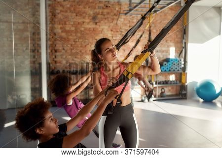 Portrait Of Female Trainer Helping Teenage Boy While He Is Training Using Fitness Straps In Gym. Foc