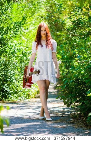 A Red-haired Beautiful Young, Romantic Girl With A Red Guitar Is Walking Along A Forest Path In Summ