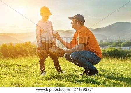 Father and son playing in baseball. Playful Man teaching Boy baseballs exercise outdoors in sunny day at public park. Family sports weekend. Father's day.