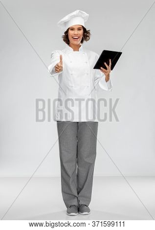 cooking, culinary and people concept - happy smiling female chef in toque with tablet pc computer showing thumbs up over grey background