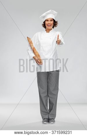 cooking, culinary and bakery concept - happy smiling female chef or baker in toque holding french bread or baguette and showing thumbs up over grey background