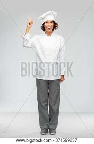 cooking, advertisement and food concept - happy smiling female chef in toque pointing finger up over grey background