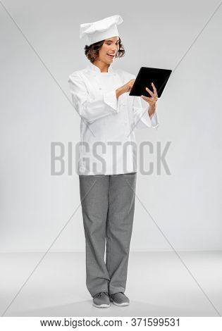 cooking, culinary and people concept - happy smiling female chef in toque with tablet pc computer over grey background