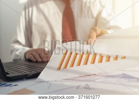 Businessman Analyzing Investment Charts With Laptop And Papers On A Sunny Day. Red Colors Of Diagram