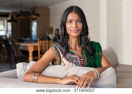 Portrait of young happy indian woman in sari at home. Beautiful girl in traditional ethnic wear with a bindi on forehead looking at camera. Smiling young woman in sari sitting on sofa.