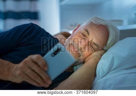 Senior man watching video on smart phone while in bed. Smiling mature man lying on bed using cellphone in the dark at home. Addict man awake using phone for chatting late in night.