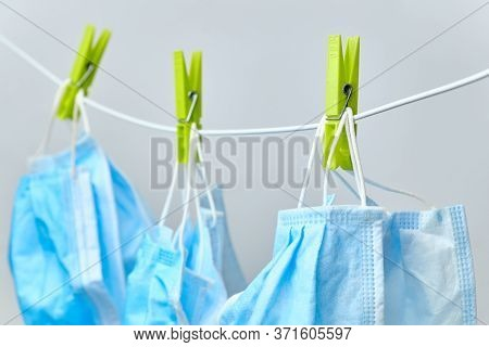 Disposable Blue Medical Surgical Mask Hanging On Peggs Clothesline For Reused After Washing. Coronav